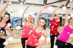 group of smiling people stretching in the gym - stock illustration