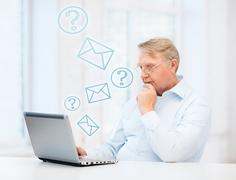 old man in eyeglasses working with laptop at home - stock illustration