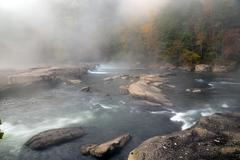 the tygart river cascades over rocks at valley falls state park - stock photo