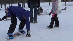 Man prepares to slide with snowboard together girl between legs Stock Footage