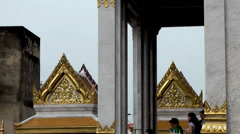 Thailand Bangkok 018 medium shot, magnificent roofs of temple behind pillars Stock Footage