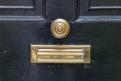 centered brass doorknob and mail slot - stock photo