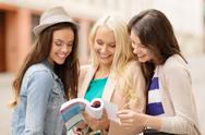 Stock Photo of beautiful girls looking into tourist book in city