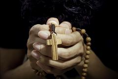 man praying with rosary - stock photo