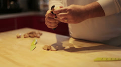 Chef peels and prepares ginger root  over butcher block Stock Footage
