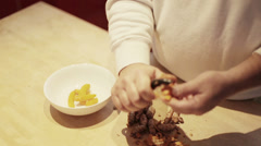 Chef peels turmeric root over butcher block Stock Footage