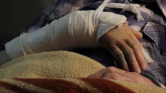 Old man, patient with broken arm lying down on table in ambulance.Close up hand. Stock Footage