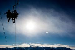 two skiers in a chairlift backlit by the sun. - stock photo
