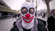 Stock Video Footage of Man with a clown mask in London close to Thames River and people passing by