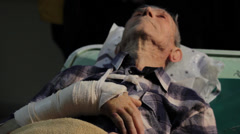 Old man, patient with broken arm lying down on hospital table in ambulance. - stock footage