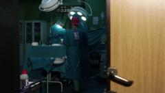 Surgeons team performing operation in hospital operating room,door opening - stock footage