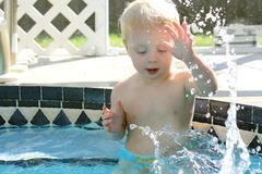Baby splashing water in backyard swimming pool Stock Photos