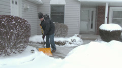 4K Man Shovels Sidewalk 3975 - stock footage