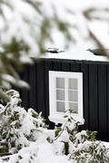 Detail Of A Black Wooden Cottage In Winter Time With One White Window - stock photo