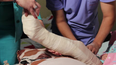 Bandage leg,technician and nurse,putting bandage, plaster,tilt up Stock Footage