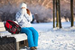 Woman with backpack heating hands in mittens at winter, copyspace Stock Photos