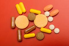different drugs isolated on red background - stock photo