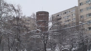 Stock Video Footage of Old Fire Tower Between Building Blocks In A Snow Storm 2