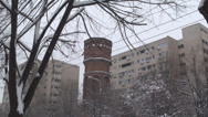 Stock Video Footage of Old Fire Tower Between Building Blocks In A Snow Storm