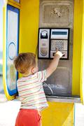 Young boy talking to the phone in a booth - stock photo