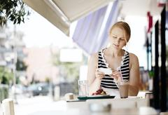 Attractive woman taking picture of a pastry on her mobile Stock Photos