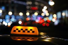 Illuminated taxi cab sign on a city street Stock Photos