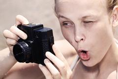 Woman pulling a comical face as she views in the viewfinder - stock photo