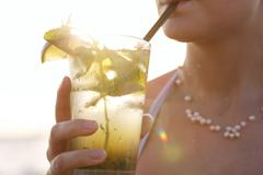 Nainen nauttia trooppisen mojito cocktail Kuvituskuvat