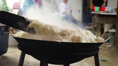 Man cooking white rice using paddle stick in a big wok, cauldron Stock Footage