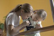 Stock Photo of Girls looking through microscope