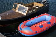 Stock Photo of A retro motorboat moored next to a new inflatable boat