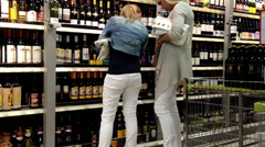 Shoppers in a grocery supermarket. Department of wines. - stock footage