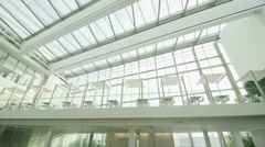 Interior view of modern office building with glass partitions & central atrium - stock footage