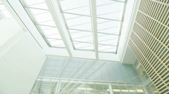 Interior view of modern office building with glass partitions & central atrium Stock Footage