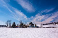 Wispy clouds over a snow covered farm in rural carroll county, maryland. Stock Photos