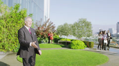 Businessmen meet and shake hands with views of the London city skyline Stock Footage