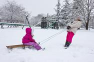 Stock Photo of two girls playing sled in the snow,