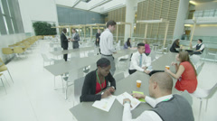 Business people take a break in large office cafe area Stock Footage