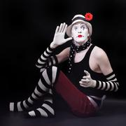 Mime in white hat with red flower sits on the floor Stock Photos