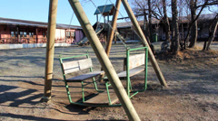 Swaying empty swing in a park. Stock Footage