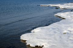 Snowy melting ice at shoreline Stock Photos