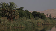 Camera boat Nile river, palm and desertic mountains Stock Footage