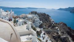 Santorini tilt-up wide from bottom of steps to top of buildings sparkling sea Stock Footage