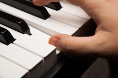 Piano keys and human finger Stock Photos