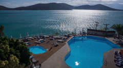 Elounda, Crete - turquoise swimming pool, sparkling sea & mountains in distance Stock Footage