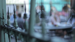 Soft focus shallow DOF bistro table people over vintage iron fence Stock Footage