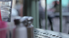 Soft focus shallow DOF setting from bistro table salt and pepper shakers Stock Footage