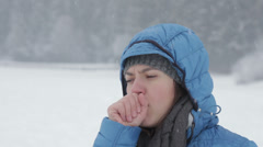 Young woman coughing in winter park  HD Stock Footage