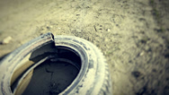 Stock Video Footage of Dolly shot of abandoned tyre on dry ground.