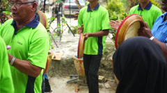Group of men and kids playing kompang while walking Stock Footage